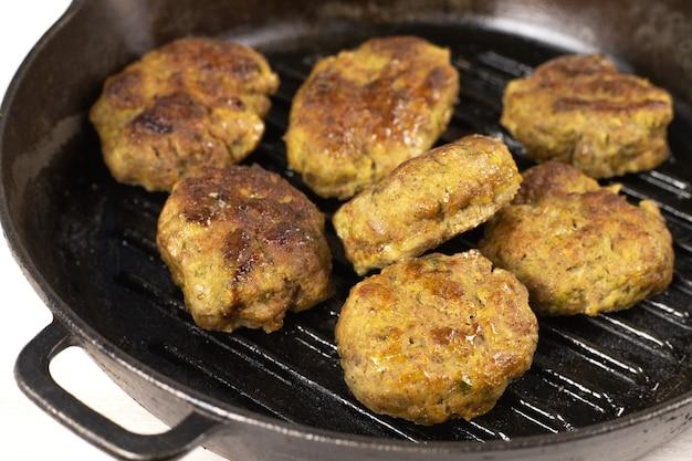 Saftige hausgemachte fleischburger pastetchen schnitzel rindfleisch, schweinefleisch, huhn, truthahn in schwarzer gusseisenpfanne auf weißem tisch. ketogenes, fleischfressendes, kohlenhydratarmes diätkonzept. nahansicht. selektiver fokus