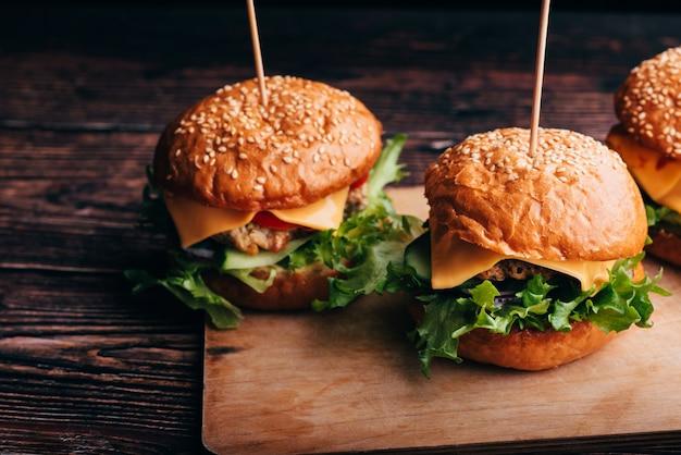 Saftige hausgemachte hamburger mit fleisch, käse, salat, tomaten auf einem brett