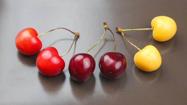 Saftige kirschbeere auf grauem hintergrund. früchte und vitamine. gesundes essen zum frühstück. früchte der vegetation. fruchtdessert