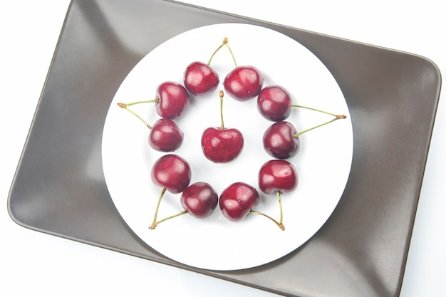 Saftige kirschbeeren liegen auf einem weißen teller. gesundes essen zum frühstück. früchte der vegetation. fruchtdessert