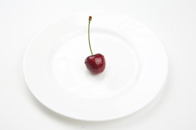 Saftige kirschbeeren liegen auf einem weißen teller. gesundes essen zum frühstück.