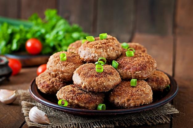 Saftige köstliche fleischkoteletts auf einem holztisch im rustikalen stil