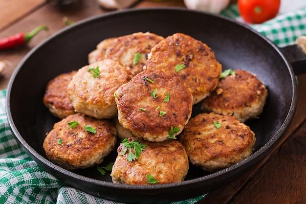 Saftige köstliche fleischkoteletts in der pfanne auf einem holztisch.