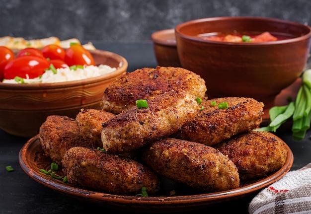 Saftige leckere fleischkoteletts auf einem dunklen tisch