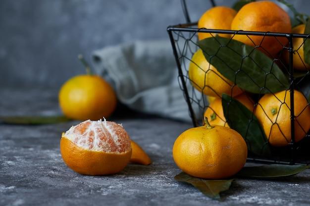 Saftige mandarinen mit blättern in einem korb