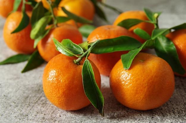 Saftige mandarinen mit grünen blättern auf dem tisch. frisch duftende mandarinen.