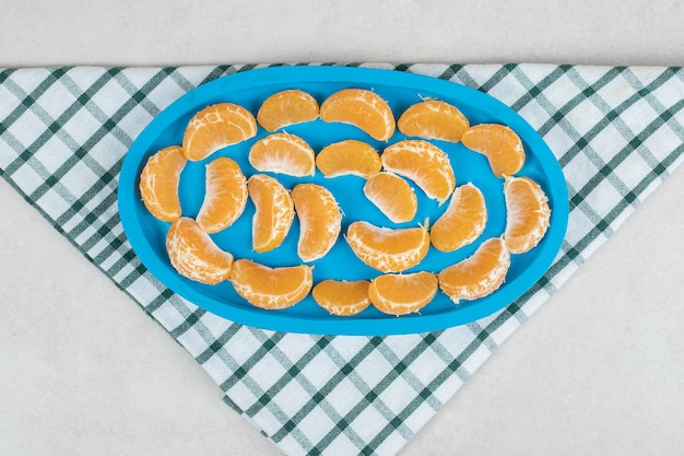 Saftige mandarinensegmente auf blauem teller