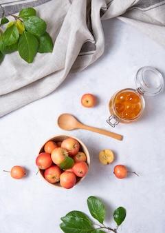 Saftige mini-äpfel in einer holzschale und einem glas marmelade