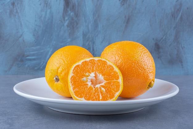 Saftige orangen auf dem teller, auf der dunklen oberfläche