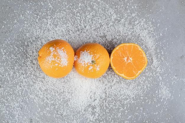 Saftige orangen, die in verstreutem kokosnusspulver auf marmortisch sitzen.
