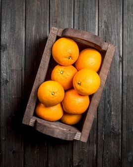 Saftige orangen in der schachtel auf schwarzem holztisch