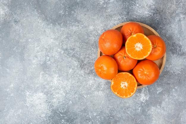 Saftige orangenfrüchte mit scheiben in einem holzteller auf steintisch.
