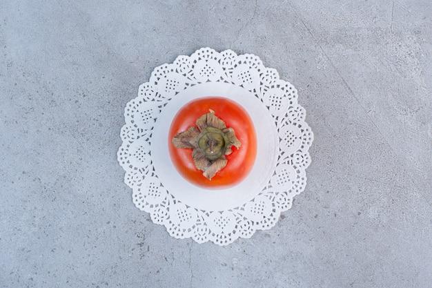 Saftige persimone auf einem deckchen auf marmorhintergrund.