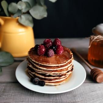 Saftige pfannkuchen mit beeren und honig auf einem weißen teller, löffel, glas, holztisch, gelbe vase mit eukalyptus. hochwertiges foto