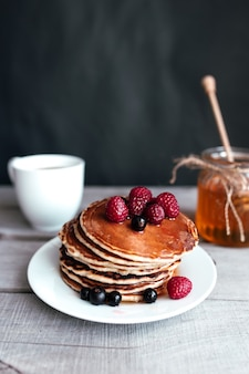 Saftige pfannkuchen mit beeren und honig auf einem weißen teller, löffel, glas, holztisch, kaffeetasse. hochwertiges foto