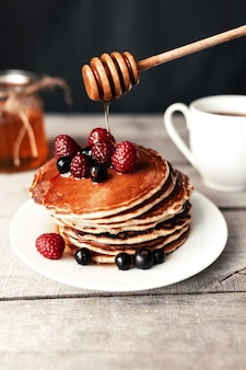 Saftige pfannkuchen mit beeren und honig auf einem weißen teller, löffel, glas, holztisch, kaffeetasse.