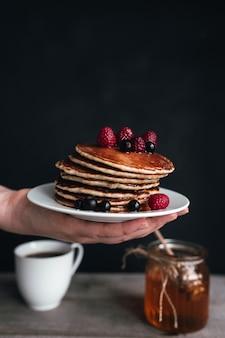 Saftige pfannkuchen mit beeren und honig auf weißem teller auf menschlicher hand, glas und löffel, holztisch mit tasse kaffee. hochwertiges foto