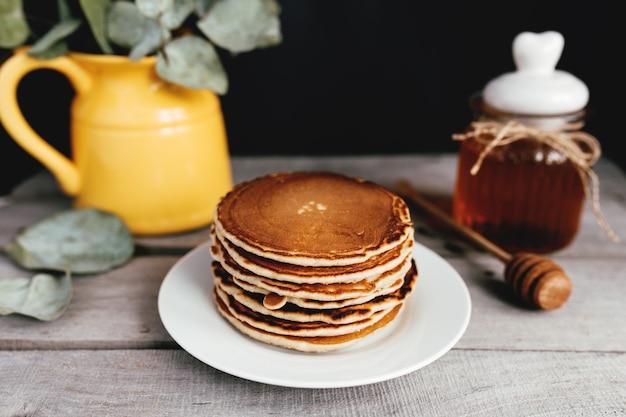 Saftige pfannkuchen mit honig auf einem weißen teller, löffel, glas, holztisch, gelbe vase mit eukalyptus. hochwertiges foto