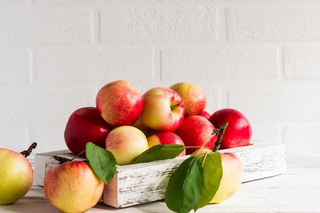 Saftige reife äpfel in einer holzkiste auf einem weißen tisch gegenüber der backsteinmauer.