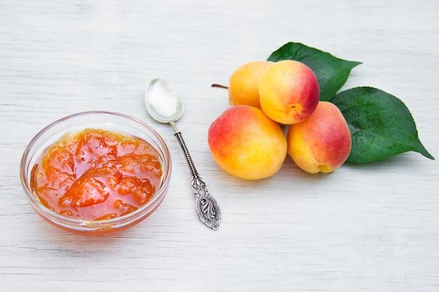 Saftige reife aprikosen und marmelade auf dem tisch