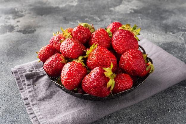 Saftige reife erdbeeren in einem teller auf einem konkreten hintergrund. süßes gesundes dessert, vitaminernte. platz kopieren.