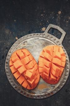 Saftige, reife mango auf einer metallplatte in würfel geschnitten