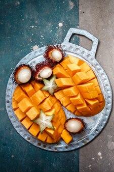 Saftige, reife mango, rambutan und cannon auf einer metallplatte