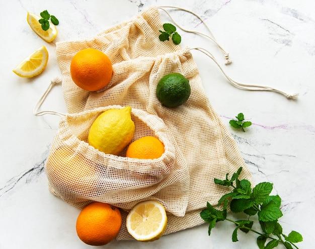 Saftige reife zitrusfrüchte in umweltfreundlichen einkaufstüten