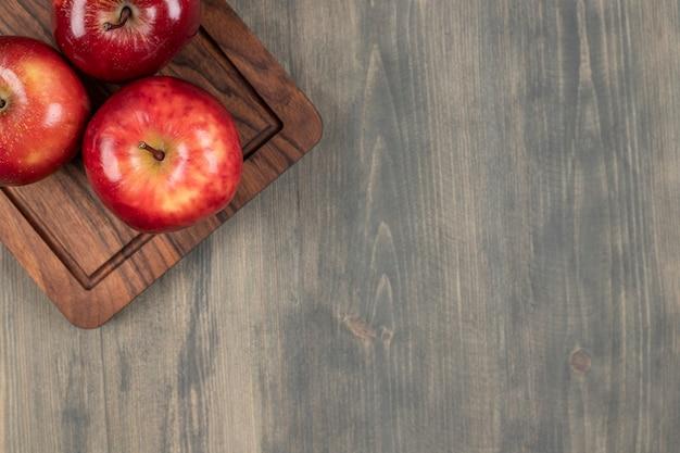 Saftige rote äpfel auf einem hölzernen schneidebrett. hochwertiges foto