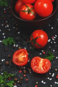 Saftige rote kirschtomaten mit gewürzen, grobem salz und gemüse. geschnittene süße und reife tomaten für salate und als zutaten zum kochen