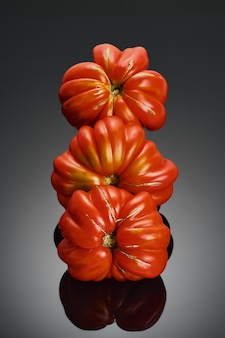 Saftige rote tomaten der sorte lorraine mit gerippter struktur aus nächster nähe, selektiver fokus. tomaten isoliert auf dunklem hintergrund, gesundes saisongemüse vom bauernmarkt, banner