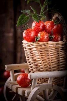 Saftige rote tomaten im korb auf holztisch, nahaufnahme