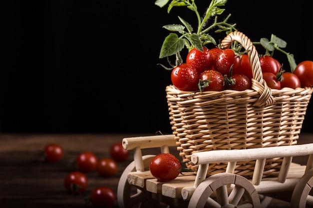 Saftige rote tomaten im korb auf holztisch