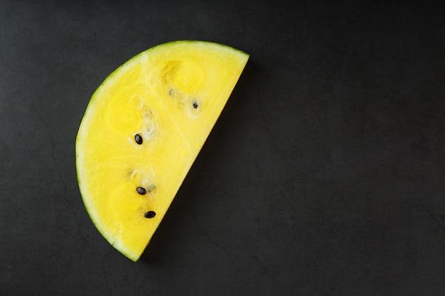 Saftige scheibe der gelben wassermelone auf steinschwarzem