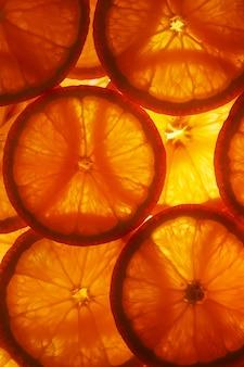 Saftige scheiben der reifen orange mit hintergrundbeleuchtung in form von geschnittenen ringen