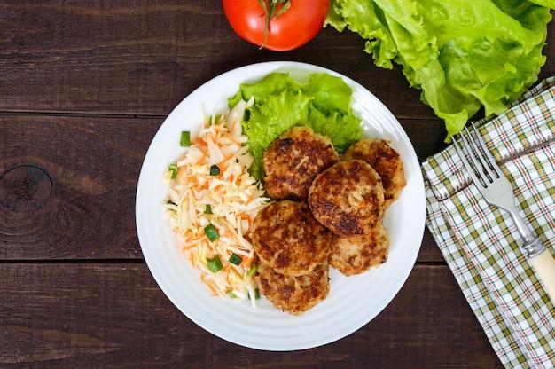 Saftige schnitzel und salat mit frischem gemüse: kohl, karotten, gemüse auf einem weißen teller. draufsicht
