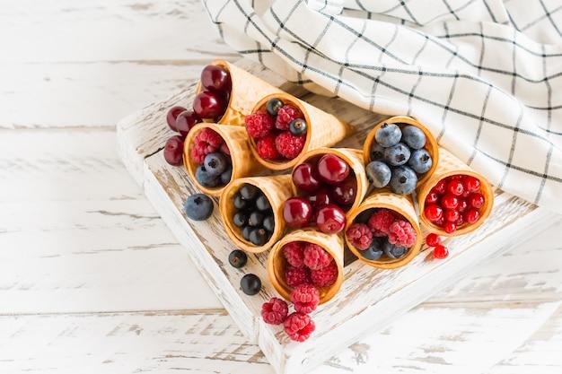 Saftige sommerbeeren in waffelkegeln in einer holzkiste mit einem handtuch. leckeres dessert.