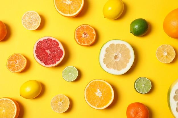 Saftige zitrusfrüchte auf gelbem hintergrund, draufsicht