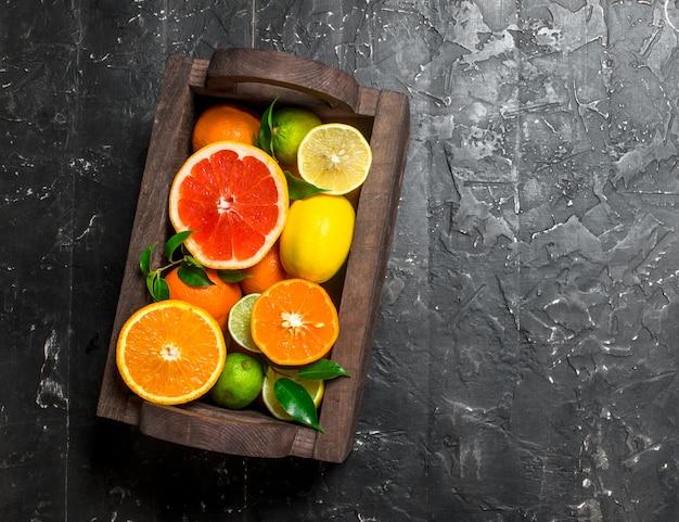 Saftige zitrusfrüchte in einer holzkiste. auf schwarzem rustikalem tisch