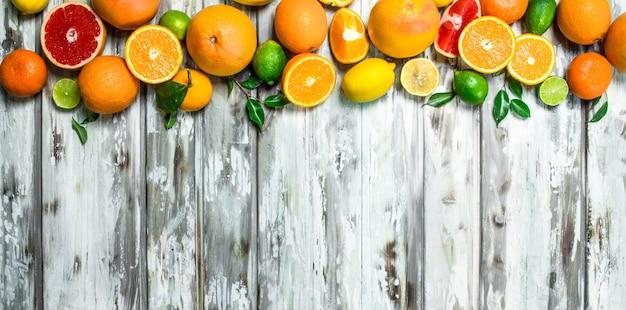 Saftige zitrusfrüchte mit blättern. auf holztisch