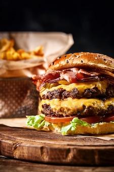 Saftiger amerikanischer burger, hamburger oder cheeseburger mit zwei rindfleischpastetchen, mit sauce und auf schwarzem hintergrund