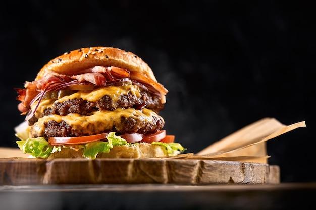 Saftiger burger auf dem brett, schwarzer hintergrund. dunkler hintergrund, fast food. traditionelles amerikanisches essen. speicherplatz kopieren.