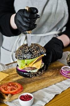 Saftiger burger in den händen des chefs. das konzept des kochens des schwarzen cheeseburgers. selbst gemachtes hamburgerrezept