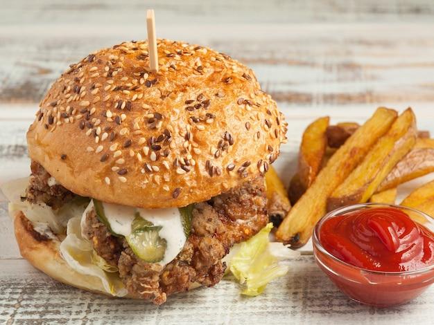 Saftiger burger mit pommes frites, gurken, kartoffeln und tomatensauce