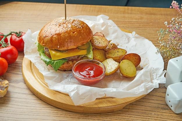 Saftiger burger mit rindfleisch, geschmolzenem käse, gurke und junger kartoffelgarnitur auf pergament. amerikanisches fast food
