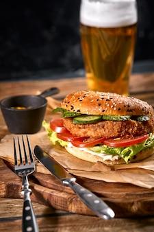 Saftiger burger, pommes frites, saucen und ein glas kaltes bier auf einem dunklen holzplatz. speicherplatz kopieren