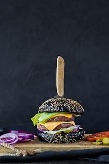 Saftiger cheeseburger auf einem hölzernen hackenden brett.