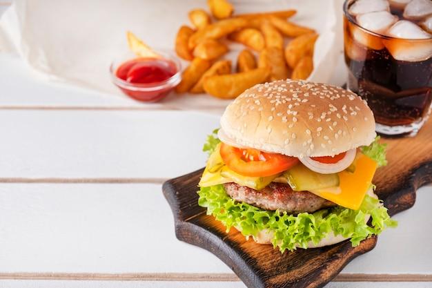 Saftiger fleischburger mit tomate, käse, zwiebel, gurke und kopfsalat. serviert mit getränk, kartoffel und ketchup. platz kopieren