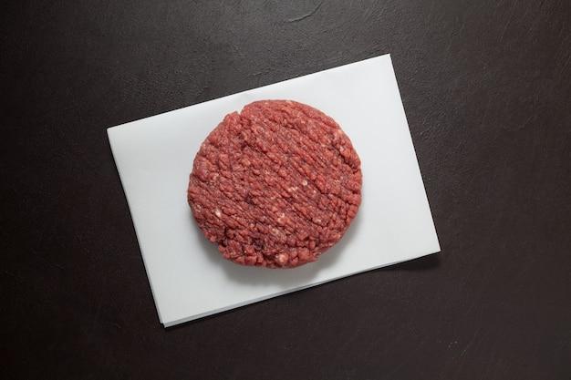 Saftiger hausgemachter hamburger. rohes hackfleisch, draufsicht.