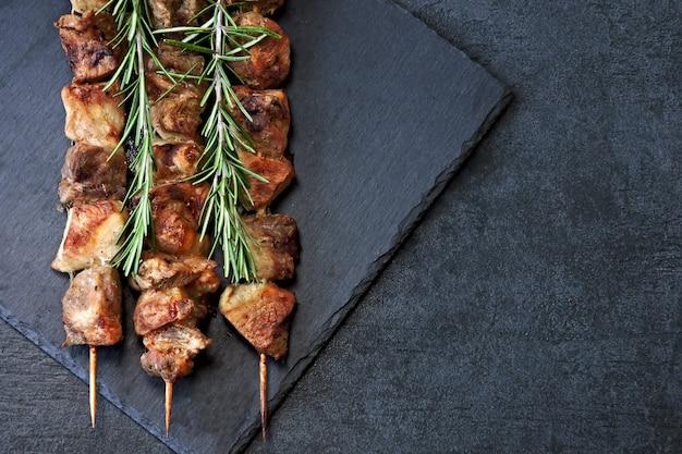Saftiger kebab mit rosmarin auf einem dunklen steinbrett.